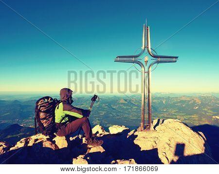 Tired Hiker Sit Bellow Crucifix On Mountain Peak. Iron Cross At Alps Mountain Top