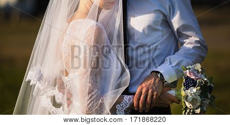 Wedding couple on nature with sunlight. Love between a man and a woman. Bride in wedding dress. The groom in a suit. Beautiful wedding bouquet. Natural summer background.