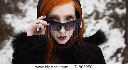 redhead stylish girl with pale skin blue eyes and burgundy red lips with a shawl on her head in a black coat on a background of a winter forest the woman with black sunglasses portrait of full-face