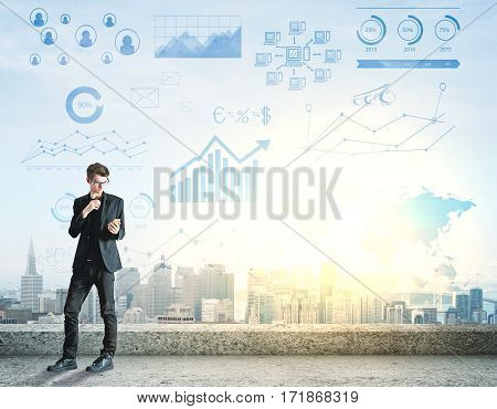 Young businessman using cellphone while standing on rooftop with city view and financial charts. Creative business ideas concept