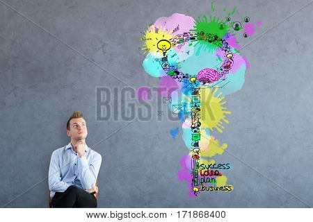 Thoughtful businessman sitting on concrete background with creative business keys sketch