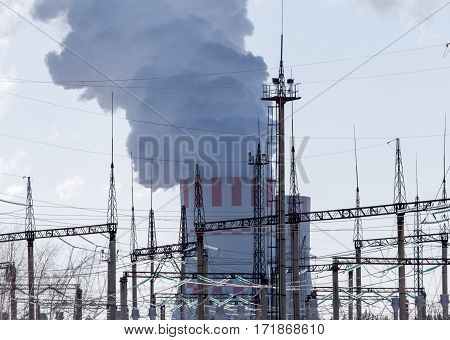 Nuclear power plant with white smoke or vapour from cooling tower and high-voltage equipment