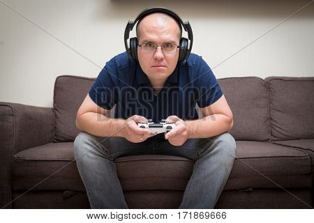 man seated on a sofa with console controller in hands and playing video games