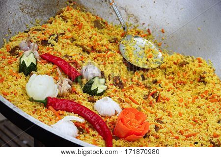 Pilaf cooked in a wok. Dish of rice, meat and vegetables cooked in a wok on fire.