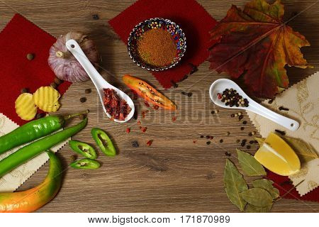 A mixture of peppers, garlic, ginger and lemon on a wooden table. Still life.