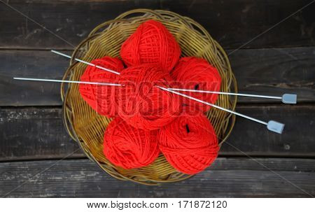Basket with some red clews and knitting needles