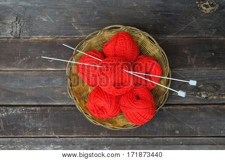 Red clews with needles in a basket on grey planks