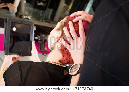 woman at the hairdresser's, talking to stylist about her new haircut color. the digital tablet is used to show her a peview of what she will look like blank screen