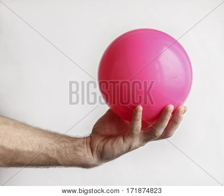 Man's hand holding a ball for gymnastics