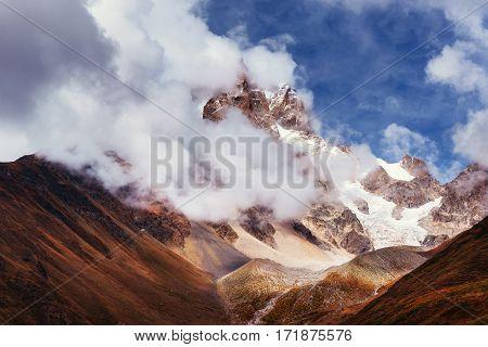 Autumn landscape and snow mountains in beautiful cumulus clouds. Main Caucasian Ridge. Type Mount Ushba Mheyer, Georgia.