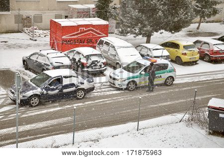 Bytca Slovakia - February 17 2017: Police traffic partol stop a car. Policeman stand outside vehicle in bad weather while snow falls.