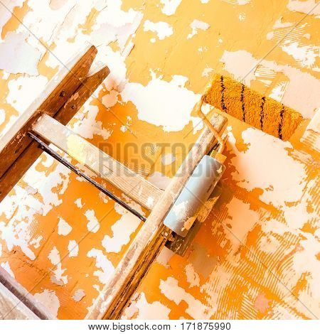 Painter wooden ladder with roller paint, leaning wall