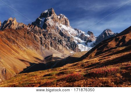 Fantastic scenery and snowy peaks in the first morning sunlight. Autumn landscape. Main Caucasian Ridge. Georgia. Europe