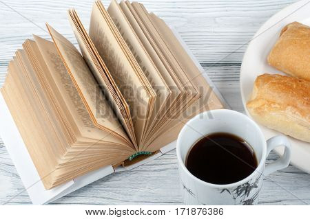 Open book coffee cup and snack on wooden table background