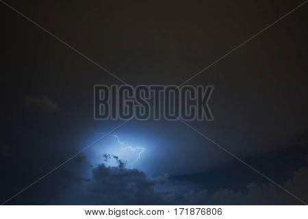 Lightning strike on the cloudy dark sky. Fantastic summer night scene.