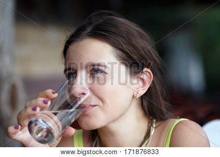 Pretty young woman drinking pure water from a transparent glass beaker. Selective focus.
