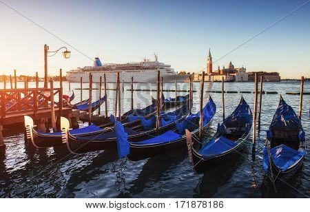 Gondolas on the huge luxury cruise ship in the Grand Canal in Venice. More than 10 million tourists visit Venice every year.