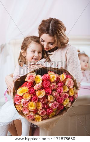 Portrait of smiling mother with daughter and bouquet of roses.