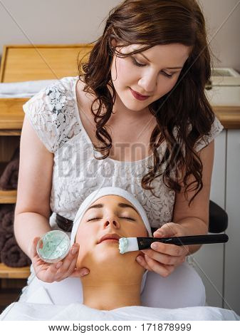Photo of a young woman getting a facial in a salon.