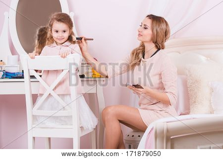 Mother and daughter doing joke make-up near dress table.