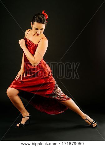 Photo of a beautiful woman dancing the tango over dark background.