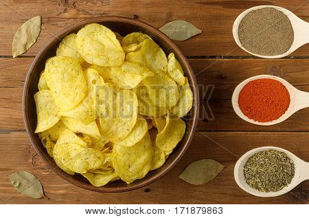 Potato Chips And Spices On A Wooden Table.