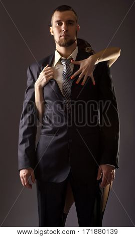 Stylish Man In A Suit And Tie On Gray Background.