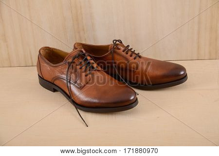 Fashion male leather brown shoes on wooden background