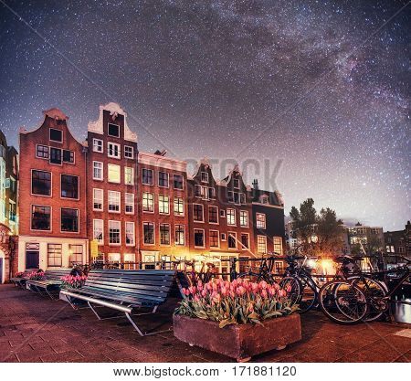 Fantastic starry sky at night in Amsterdam. Beautiful illumination of buildings near the water in the channel. Art photography