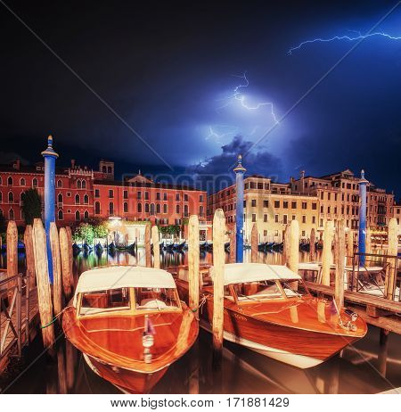 Exciting sky with lightning. The water from boats and gondolas in the background. The colorful facades of old medieval buildings. Venice. Italy. Europe