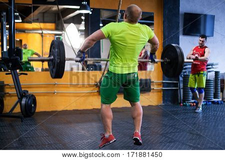 Athletic man performing a barbell snatch at the gym, view from the back