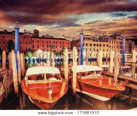 City landscape. Venice at sunset. Green water with boats and gondolas in the background. The colorful facades of old medieval buildings. Italy. Europe