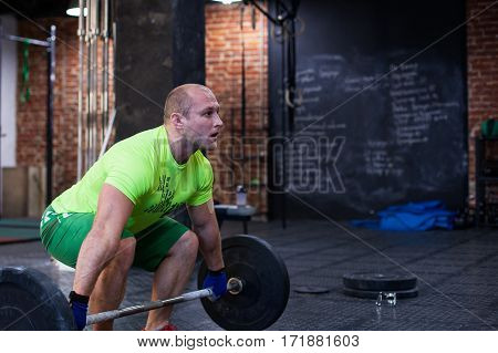 Athletic man is lifting up the barbell at the gym