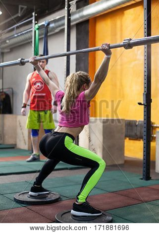 Athletic woman is squatting with a barbell under the trainer's supervision