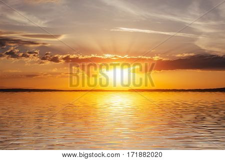 Sunset over the sea, the sea coast. West fireball of the sun above the horizon in a colorful orange sky. Fantastic cumulus