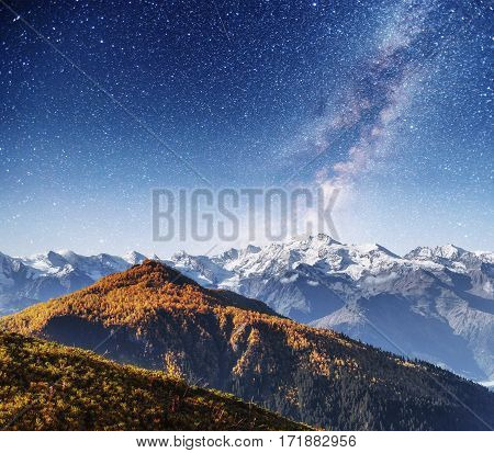 Fantastic starry sky. Autumn landscape and snow-capped peaks. Main Caucasian Ridge. Europe.