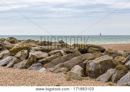 Rocky separation on the beach. Beach scene on the coast in Sussex near Brighton and shows a simple rocky outcrop on a beach withthe sea sun and a sail boat on the horizon.