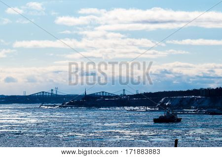 The St-Lawrence River with Quebec's bridges during a bright winter day near Levis, Quebec, Canada.