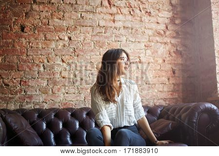 Young attractive brunette woman sit on the leather red sofa in modern loft room and look to the window. Brightenning effect. Dreaming concept.