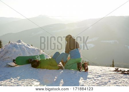 Skier examines the leg snowboarder, which lies on the snow after a fall in Carpathians, Bukovel