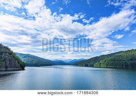 Photo of vidraru lake in fagaras, created on the dam in carpathian, blue sky and bog white clouds, chain of mountains, Romania