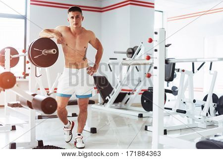 Beautiful man with big muscles, posing for the camera at the gym.