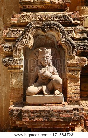 A small sculpture in a niche of the wall - a fragment of a pagoda in Bagan, Myanmar (Burma)