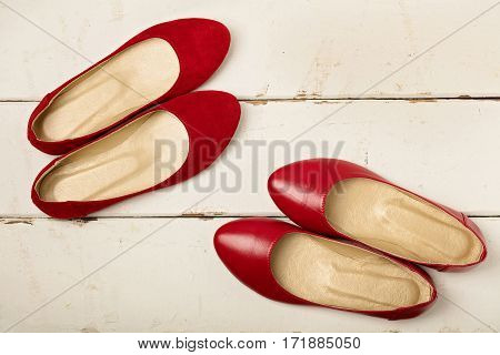 Red suede and leather women's shoes (ballerinas) on wooden background. Selective focus.