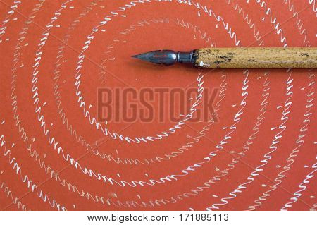 Fountain pen on red textured paper background with abstract letters pattern. Vintage design writing accessories macro view, shallow depth of field photo.