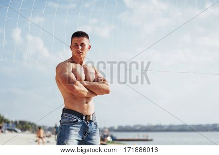 Beautiful athletic bodybuilder guy, carries out exercises with dumbbells in the gym. Sport. Fitness.