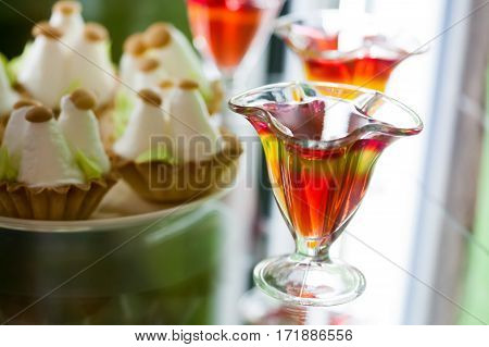Red yellow jelly in glass cup, citrus fruit gelatin dessert, cake background. macro soft focus