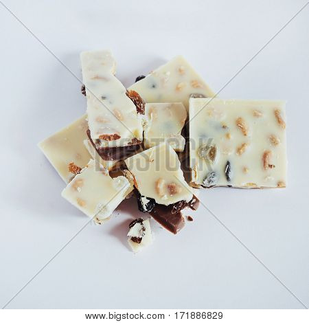 white chocolate with nuts, raisins on a white background.
