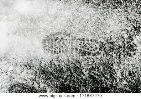 Shoe print in the snow covering asphalt.