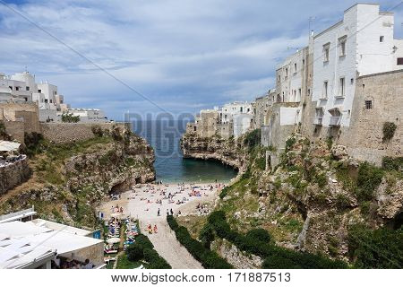Polignano a Mare, Italy - June 3, 2016: People bathing in the Mediterranean Sea at the city beach of Polignano a Mare beach town in Puglia southern Italy.